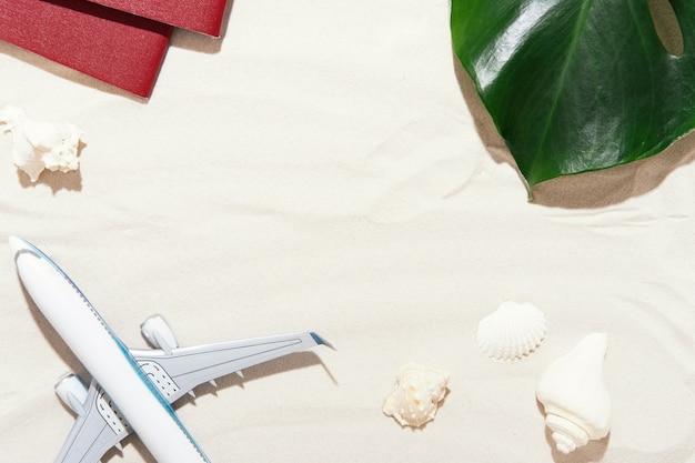 Bovenaanzicht van de achtergrond van de reiziger op tropisch zand, schelpen en vliegtuig. achtergrond voor zomervakantie vakantie reizen reis met palm schaduwen. plat leggen, ruimte kopiëren