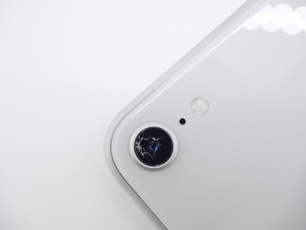 Bovenaanzicht van de achterkant van witte moderne smartphone met een gebroken camera glas close-up geïsoleerd op een wit oppervlak