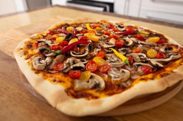 Bovenaanzicht van de afgewerkte pizza die zojuist uit de oven is gehaald.