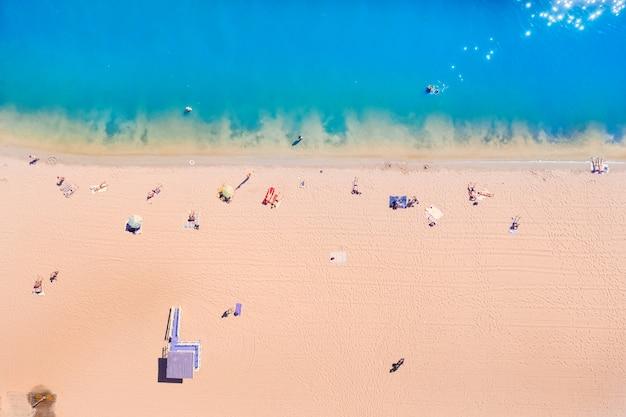 Bovenaanzicht van de azuurblauwe resortzee met prachtig water en mensen die op de kust rusten. geel warm zand en azuurblauw schoon water.