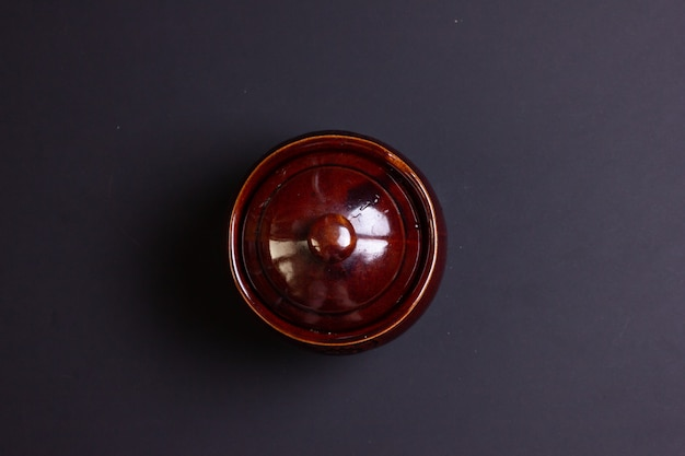 Bovenaanzicht van de bakpot. een pot met eten op een zwarte achtergrond. vrije ruimte voor de inscriptie.