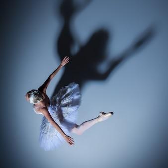 Bovenaanzicht van de ballerina in de rol van een witte zwaan op blauwe achtergrond