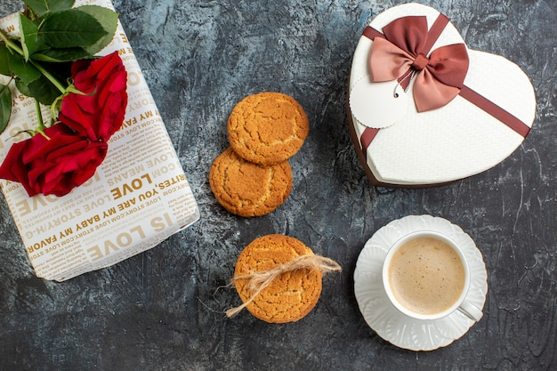 Bovenaanzicht van de beste verrassing met mooie geschenkdozen en een kopje koffiekoekjes rode rozen voor geliefde op ijzig donker oppervlak