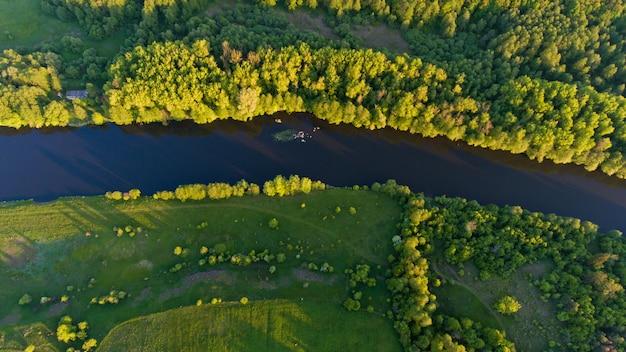 Bovenaanzicht van de bomen en de rivier bij zonsondergang