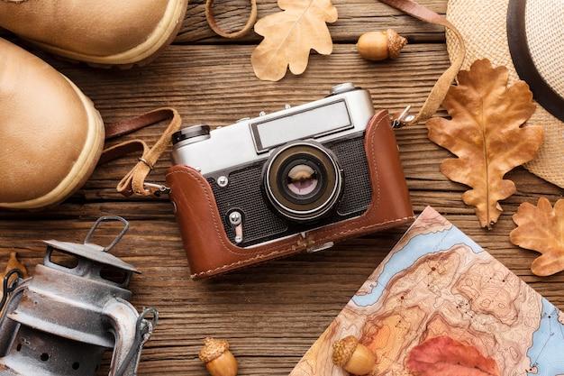Bovenaanzicht van de camera met herfstbladeren en laarzen
