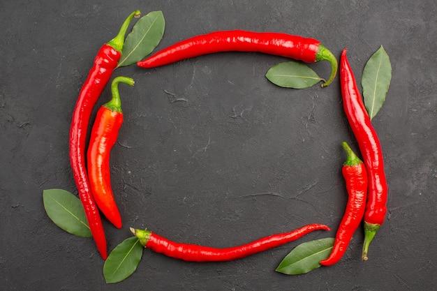 Bovenaanzicht van de cirkel van roodgloeiende pepers en loonblaadjes op een zwarte tafel