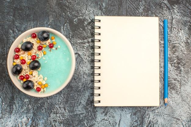 Bovenaanzicht van de close-up bessen blauwe kom van de smakelijke rode aalbessen en druiven potlood notebook