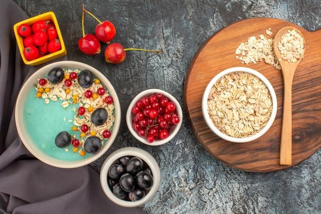 Bovenaanzicht van de close-up bessen havermout op het bord kleurrijke bessen granaatappel op het tafellaken