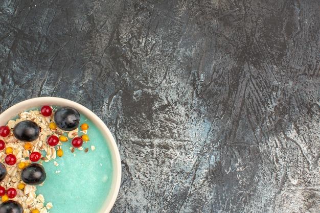 Bovenaanzicht van de close-up bessen, rode aalbessen en druiven in de blauwe kom