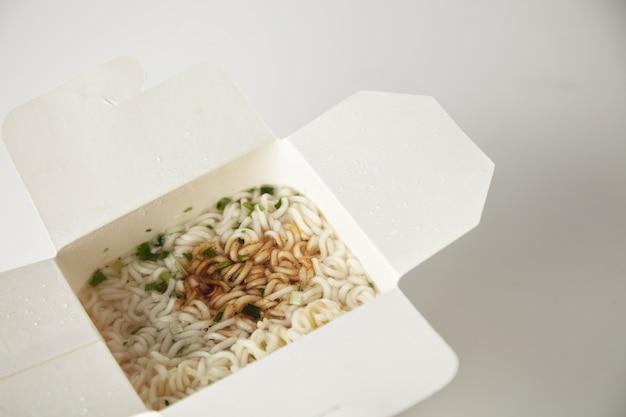 Bovenaanzicht van de close-up op smakelijke noedelsoep met pasta en sojasaus in lege afhaalmaaltijden kartonnen doos geïsoleerd op wit