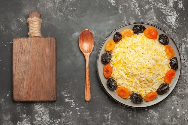 Bovenaanzicht van de close-up rijst de snijplank lepel rijst met gedroogde vruchten in de plaat op tafel