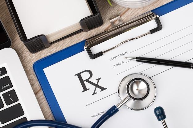 Bovenaanzicht van de close-up van de werkplek van de farmaceutische chemicus. stethoscoop, laptop en leeg receptformulier op houten oppervlak. gezondheidszorg, medisch en farmaceutisch concept.