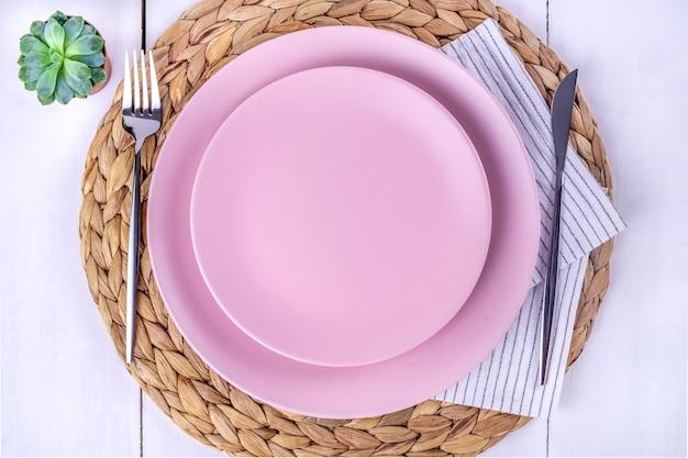 Bovenaanzicht van de close-up van een portie van twee lege roze borden, een mes en een vork op een eco-vriendelijke servet van stro. selectieve aandacht. mockup, minimalisme.