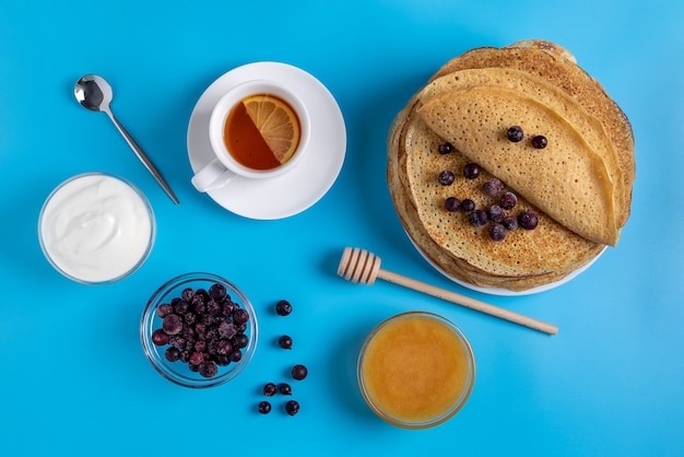 Bovenaanzicht van de close-up van russische nationale keuken en dessert pannenkoeken met zure room, bessen en honing. traditioneel gerecht voor vastenavond. selectieve aandacht.