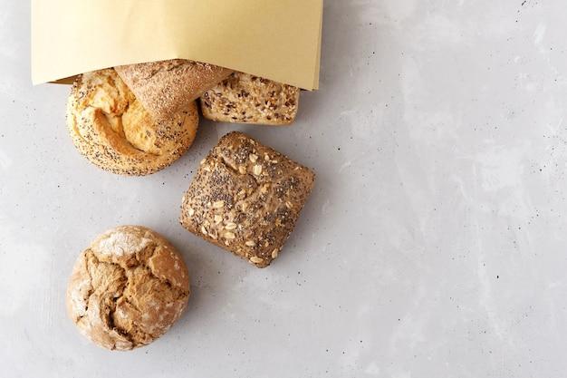 Bovenaanzicht van de close-up van verse verschillende broodjes verspreid vanuit een papieren zak op een tafel