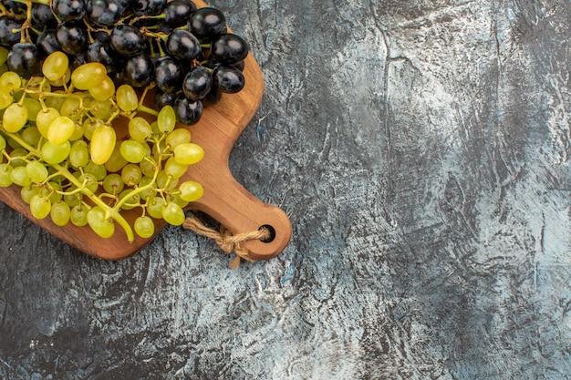 Bovenaanzicht van de druiven de smakelijke groene en zwarte druiven op het keukenbord