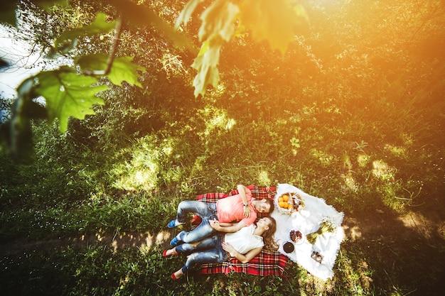 Bovenaanzicht van de gelukkige paar liggend op het gras op een zonnige dag