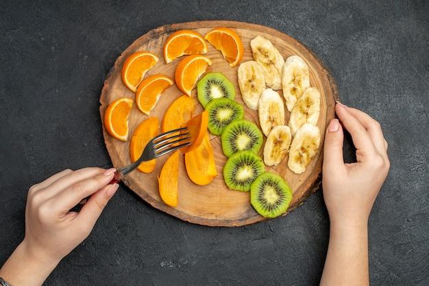 Bovenaanzicht van de hand die natuurlijk biologisch vers fruit neemt met een vork op een snijplank op een donkere achtergrond