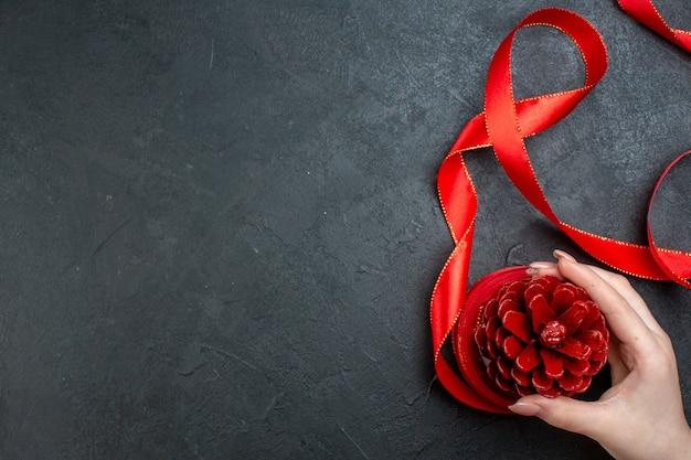 Bovenaanzicht van de hand met een coniferenkegel met rood lint op donkere achtergrond