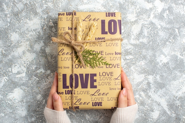 Bovenaanzicht van de hand met een groot ingepakt cadeau voor kerstmis op een ijsoppervlak