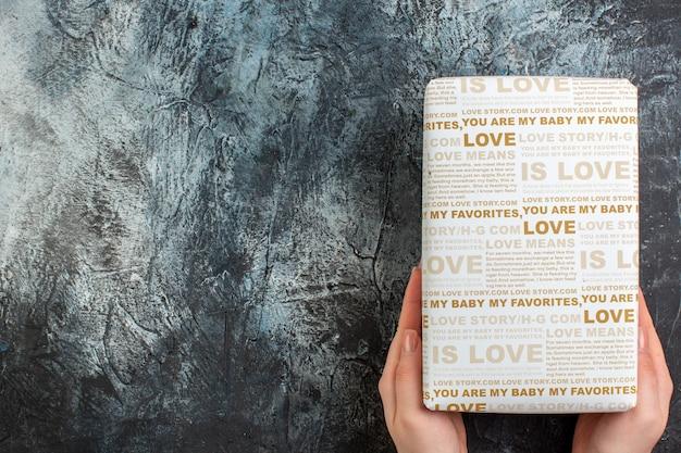 Bovenaanzicht van de hand met een mooie geschenkdoos voor de geliefde op een donkere achtergrond met vrije ruimte