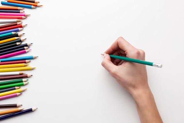 Bovenaanzicht van de hand met potlood op papier