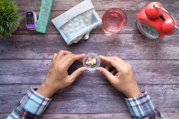Bovenaanzicht van de hand van de man die medicijnen op tafel neemt