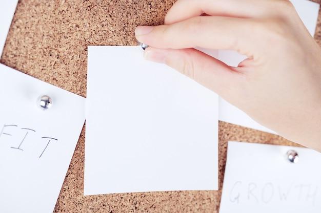 Bovenaanzicht van de hand van de persoon die een herinneringsnotitie aan het kurkbord bevestigt. corticale plank met vellen papier. lege plaats voor tekst of creatief ontwerp. mockup-stijl.