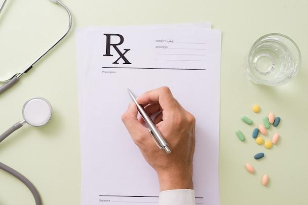 Bovenaanzicht van de hand van een arts die een recept schrijft. op het bureau staan ook een pillenflesje en een stethoscoop.