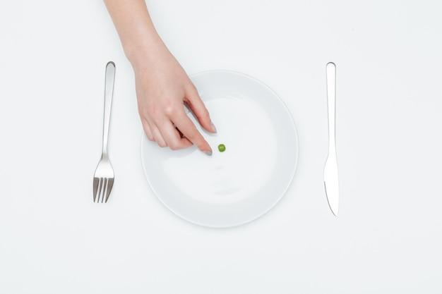 Bovenaanzicht van de hand van een jonge vrouw die een groene erwt van het bord neemt