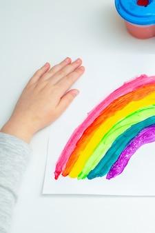 Bovenaanzicht van de hand van een kind met geschilderde regenboog op wit papier tijdens de covid-19-quarantaine thuis. de creativiteit van kinderen.