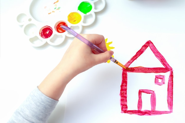Bovenaanzicht van de hand van een kind met penseel is een tekening van een landhuis door waterverf op wit papier. zijaanzicht.
