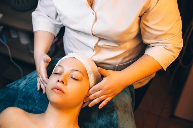 Bovenaanzicht van de hand van een schoonheidsspecialist die gezichtsmassage doet na huidverzorgingsmasker op een vrouwelijk gezicht.