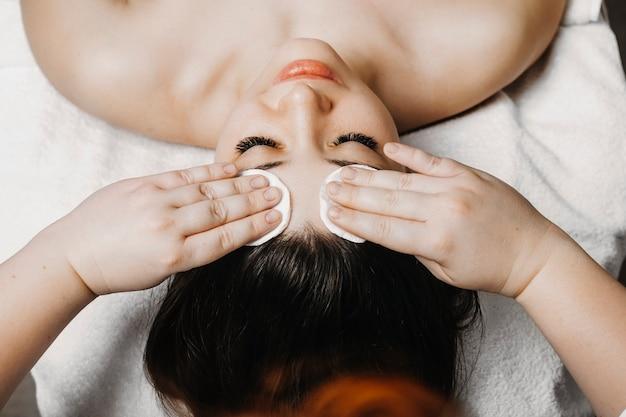 Bovenaanzicht van de hand van een schoonheidsspecialist die huidverzorgingsroutine doet voor gezichtsbehandeling op een schattig vrouwelijk gezicht in het wellnesscentrum.