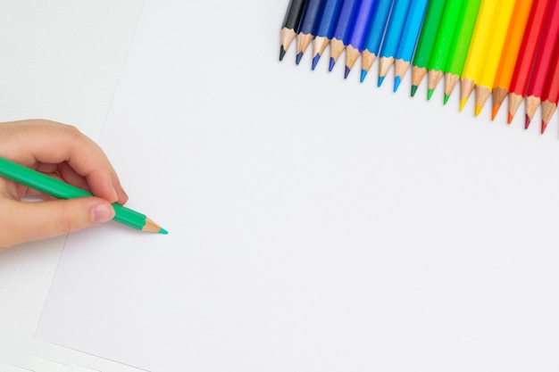 Bovenaanzicht van de hand van het kind op een leeg wit vel papier met een set kleurpotloden. ruimte voor tekst kopiëren.