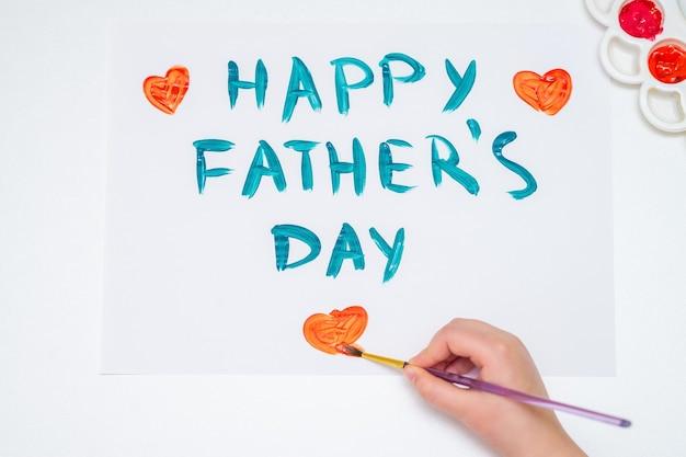 Bovenaanzicht van de hand van het kind tekenen rood hart met tekst happy father's day wenskaart op wit papier. gelukkig vaderdagconcept.