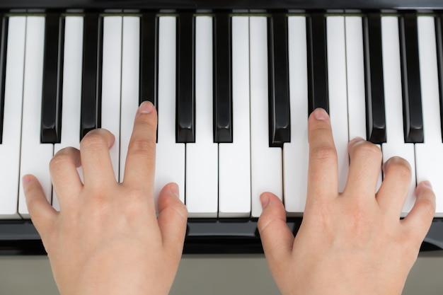Bovenaanzicht van de handen spelen piano