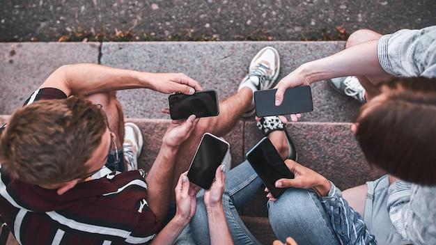 Bovenaanzicht van de handen van de mensen met telefoons die dicht bij elkaar zitten