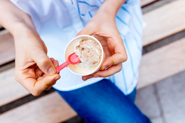 Bovenaanzicht van de handen van de vrouw met een bak ijs met een lepel