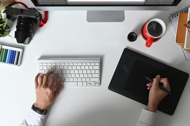 Bovenaanzicht van de handen van een grafisch ontwerper is typen op toetsenbord en werken op grafisch tablet