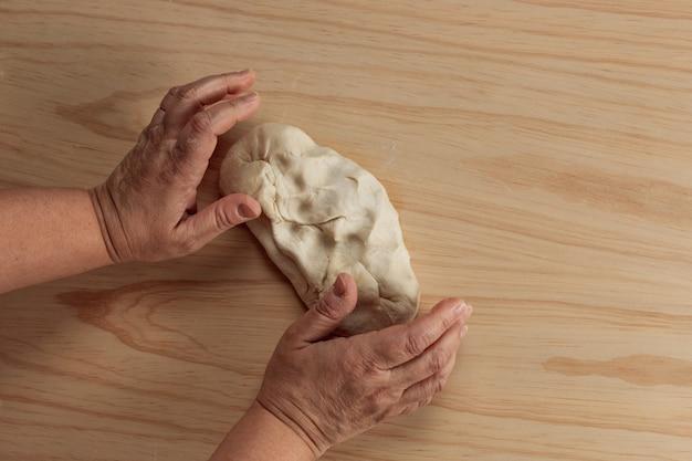 Bovenaanzicht van de handen van een volwassen vrouw kneden pizzadeeg in een houten tafel in de keuken