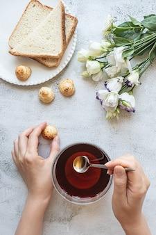 Bovenaanzicht van de handen van een vrouw met een kopje theekoekjes geroosterd brood en bloemen