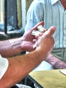 Bovenaanzicht van de handen van mensen die dominostenen spelen