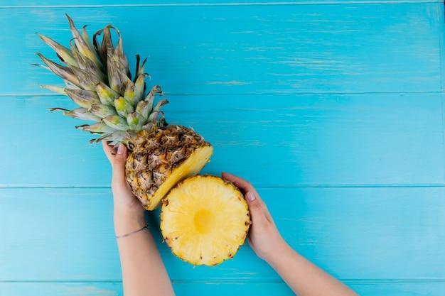 Bovenaanzicht van de helft gesneden ananas op blauwe achtergrond met kopie ruimte