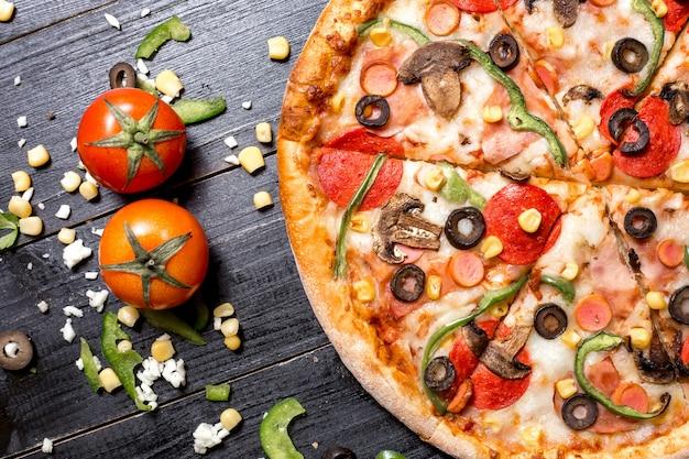 Bovenaanzicht van de helft van de pepperoni pizza geplaatst naast tomaten, kaas, maïs en paprika