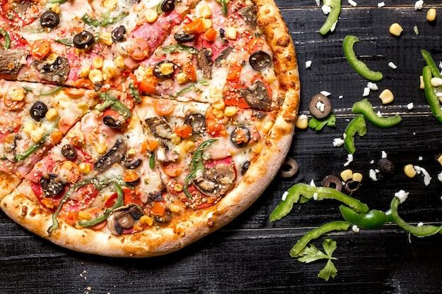 Bovenaanzicht van de helft van de pepperoni pizza met sesam hagelslag