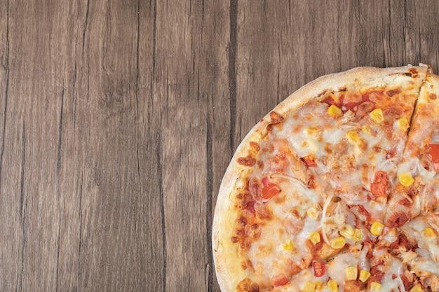 Bovenaanzicht van de helft van mozzarella pizza op houten plaat.