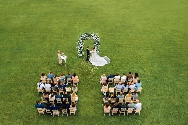Bovenaanzicht van de huwelijksceremonie in een groen veld met gasten die op stoelen zitten. trouwlocatie op het groene gazon.