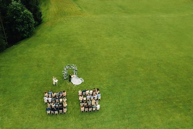 Bovenaanzicht van de huwelijksceremonie in een groen veld met gasten die op stoelen zitten