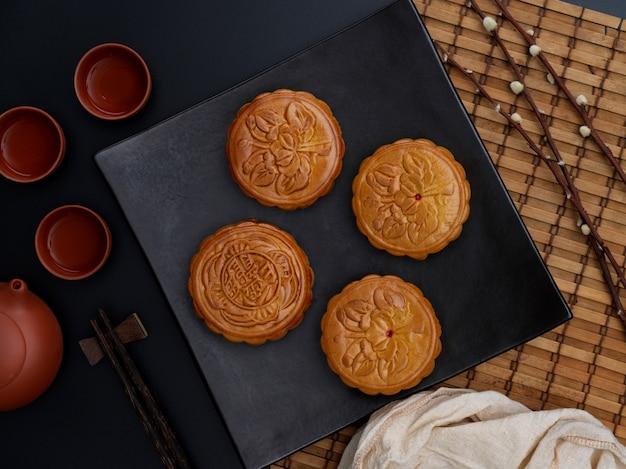 Bovenaanzicht van de instelling van de tabel met traditionele maancakes en theeservies in maanfestival. chinees karakter op de maancake vertegenwoordigt